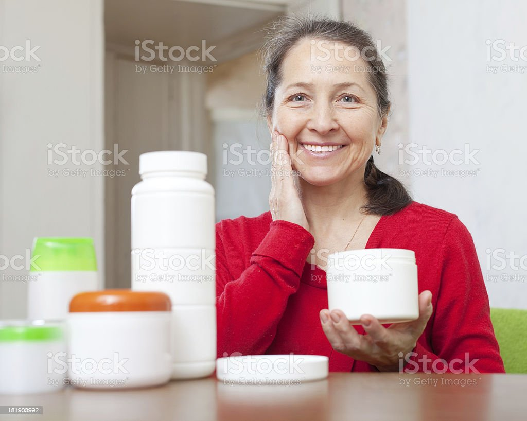 mature woman uses cosmetic cream royalty-free stock photo