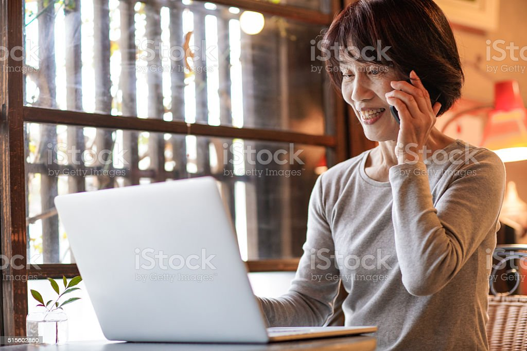 Mature woman using a computer while talking on the phone stock photo