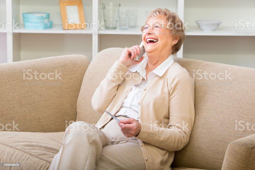 Mature woman using a cordless phone stock photo