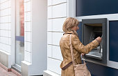Mature woman using a credit card on ATM