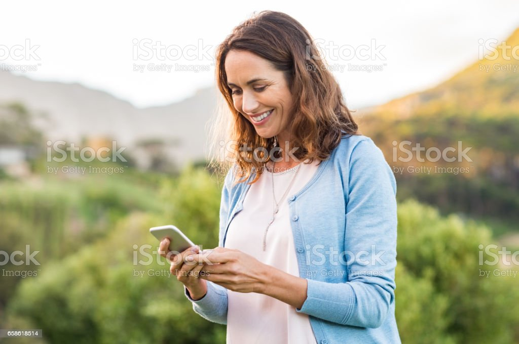 Mature woman using cellphone stock photo