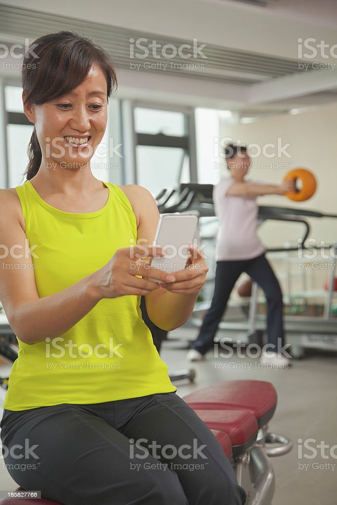 Mature woman using her cell phone in the gym royalty-free stock photo