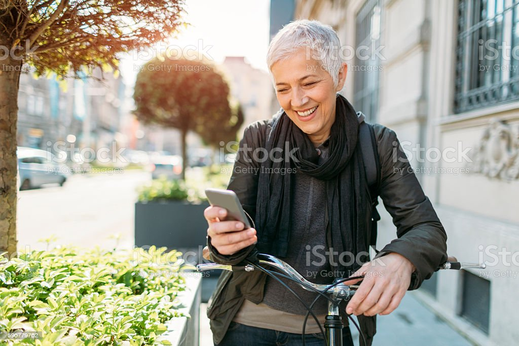 Mature Woman Using Her Smart Phone On Bicycle. stock photo