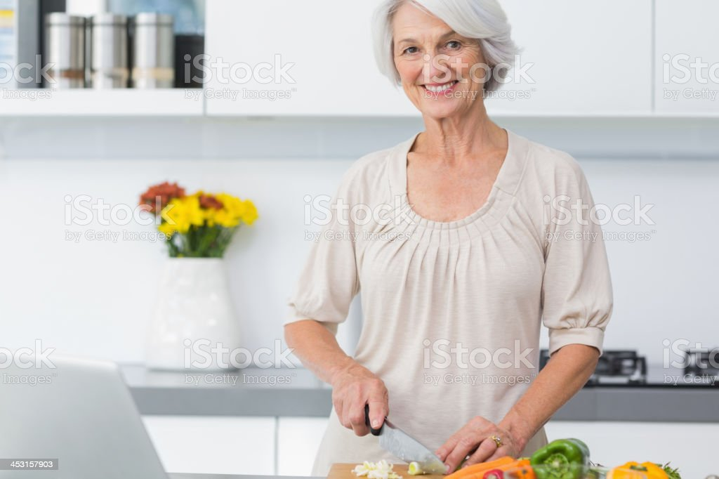 Mature woman using knife for preparing vegetables royalty-free stock photo