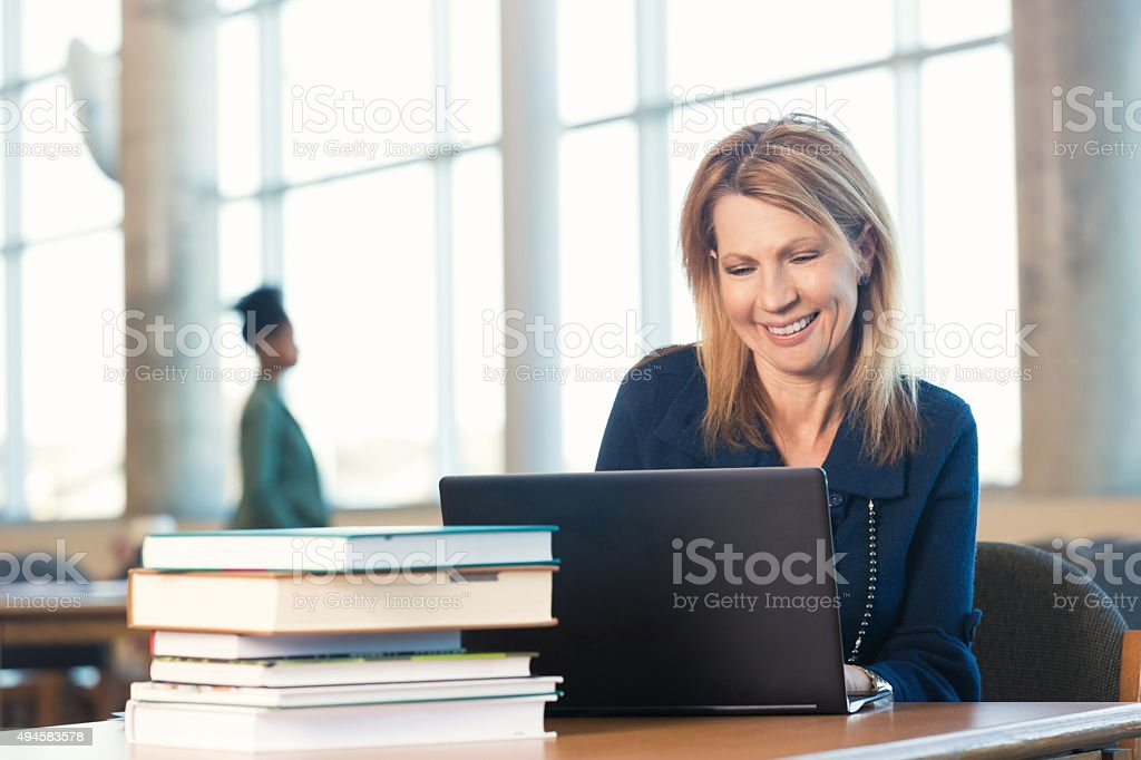 Mature woman using laptop, studying in modern library stock photo