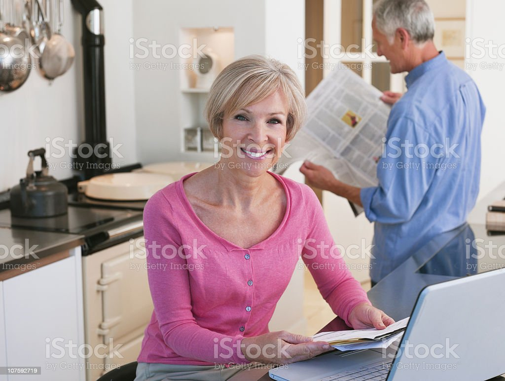 Mature woman using laptop with senior man in background reading newspaper royalty-free stock photo