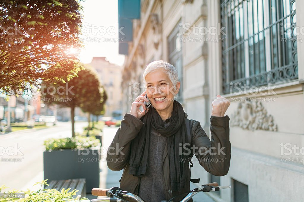Mature Woman Using Phone On Her Bicycle. stock photo