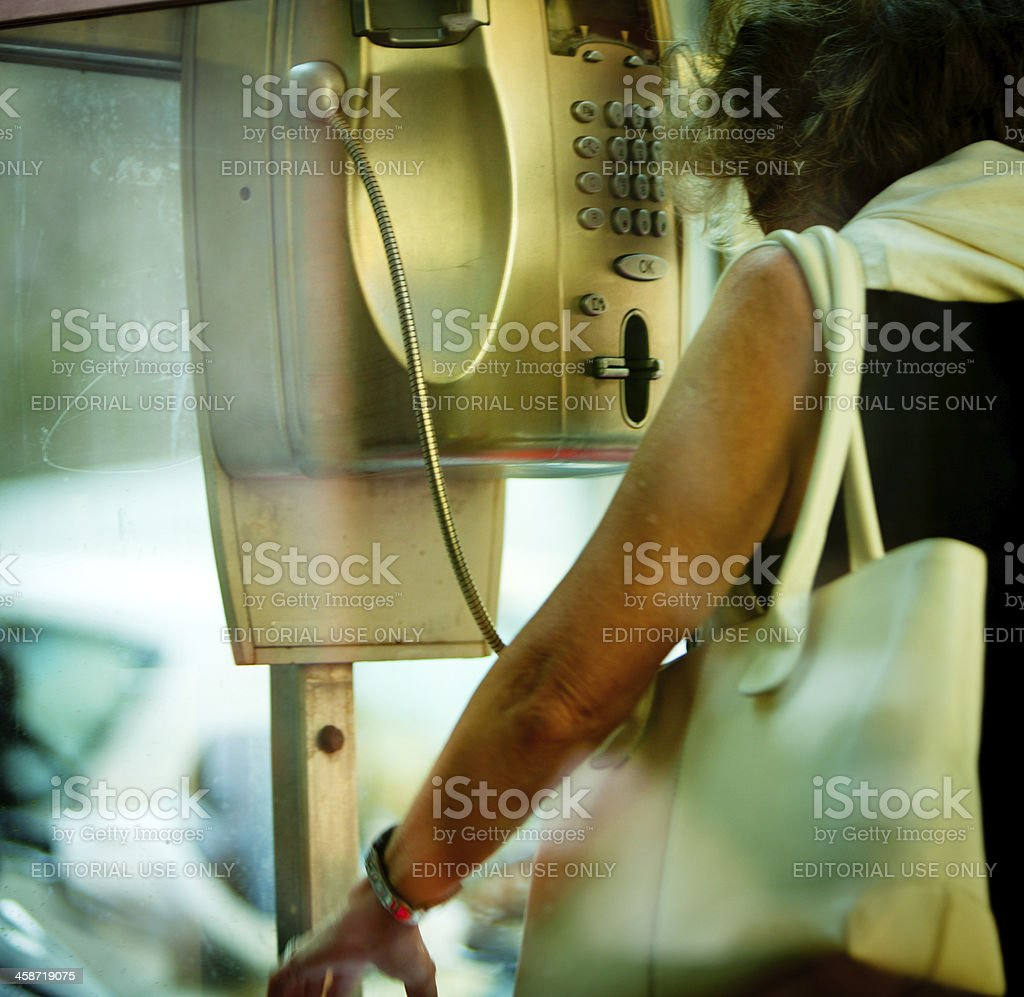 Mature woman using public phone on Milan street royalty-free stock photo