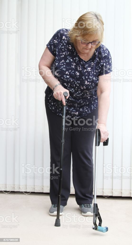 Mature woman using reaching aid or grabber stock photo