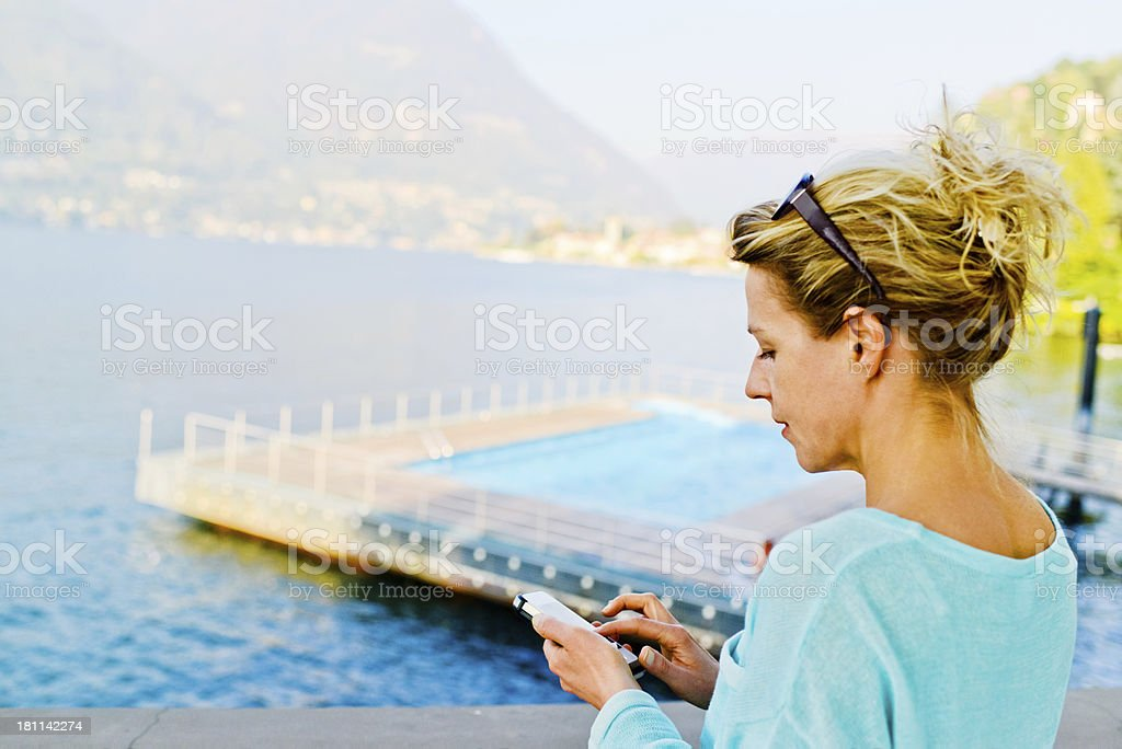 Mature Woman using smartphone enjoying view on Lake Como royalty-free stock photo