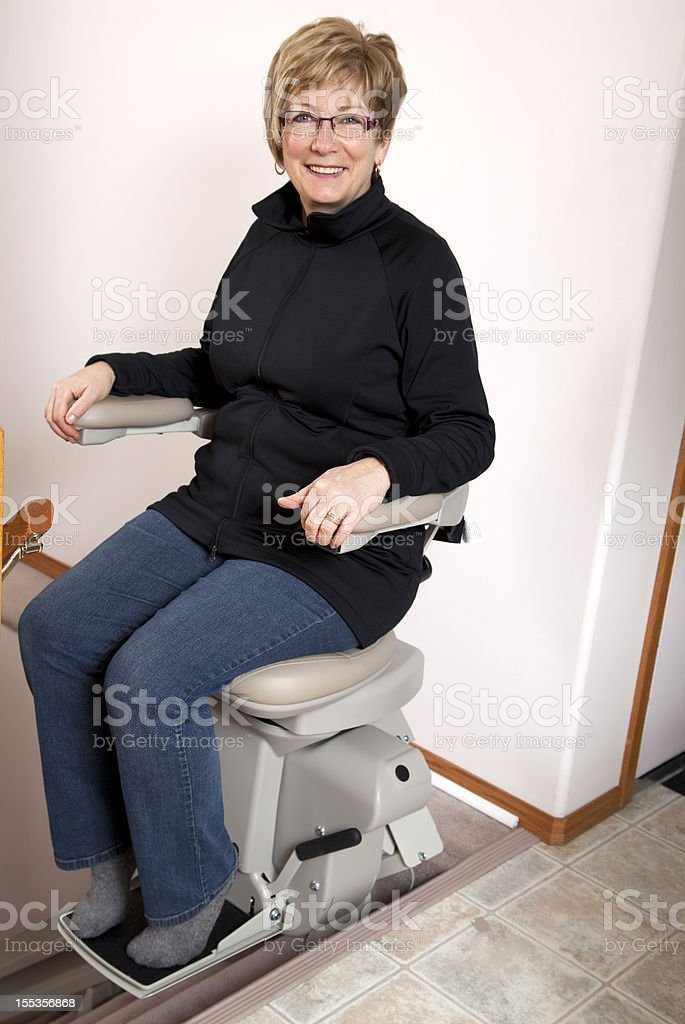 Mature woman using stairlift: Assisted Living stock photo