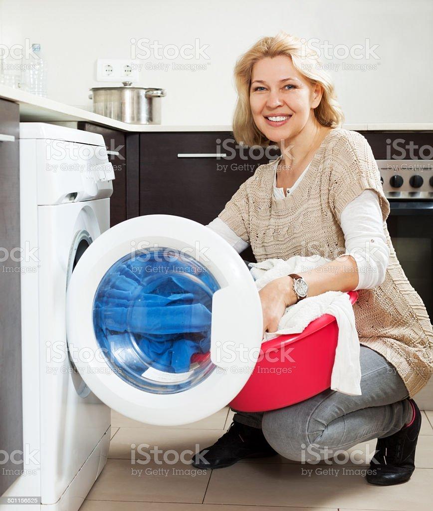 mature woman using washing machine at home stock photo
