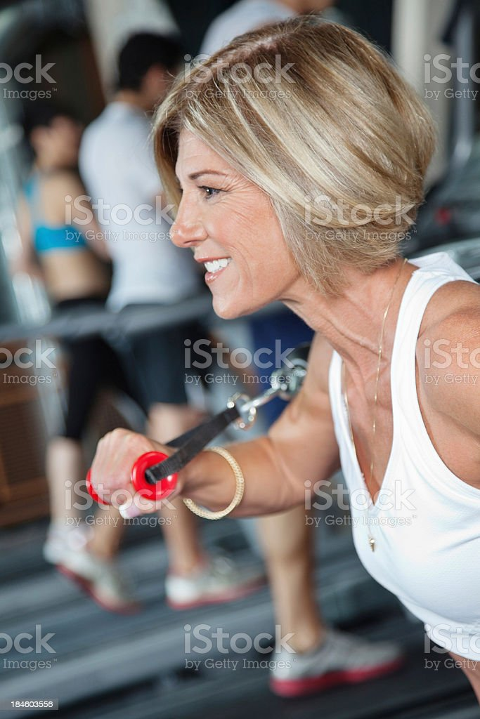 Mature woman using weight machines at the gym royalty-free stock photo