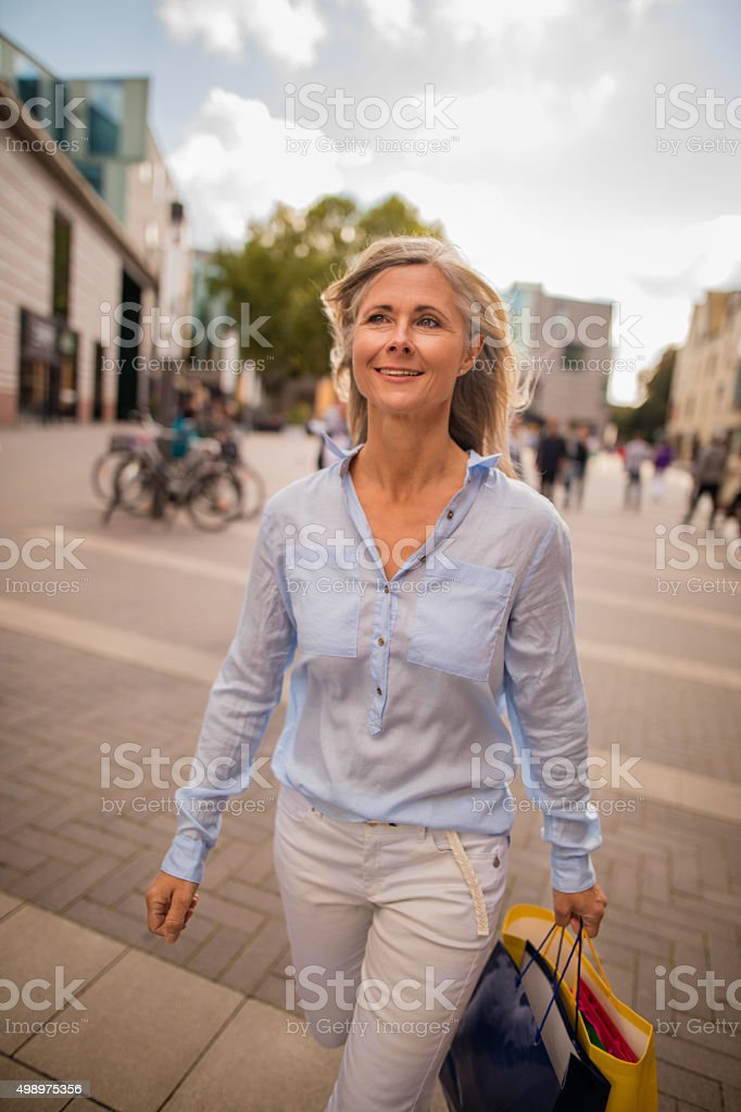 Mature woman walking confidently on a city street stock photo