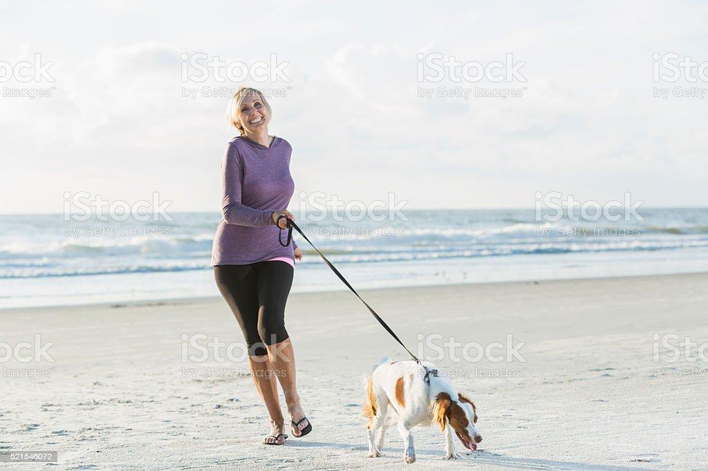Mature woman walking dog on beach stock photo