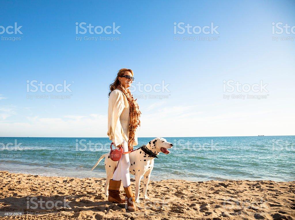 Mature woman walking her dalmatian dog by the beach stock photo