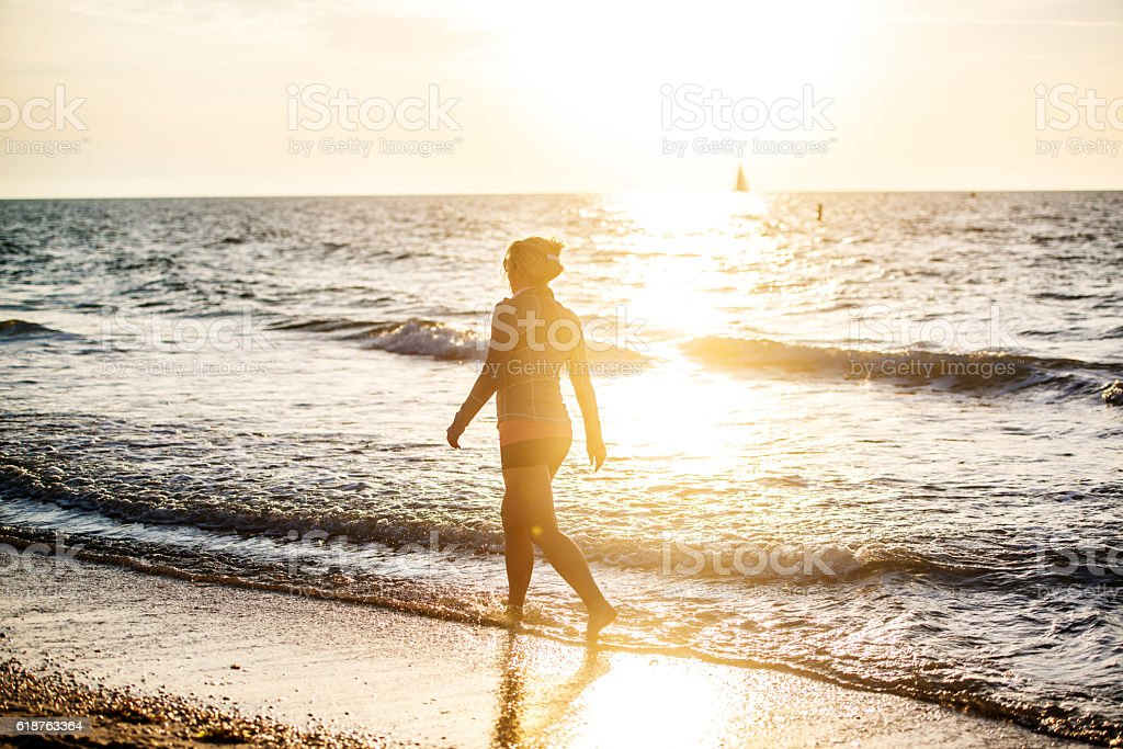 Mature woman walking on the beach stock photo