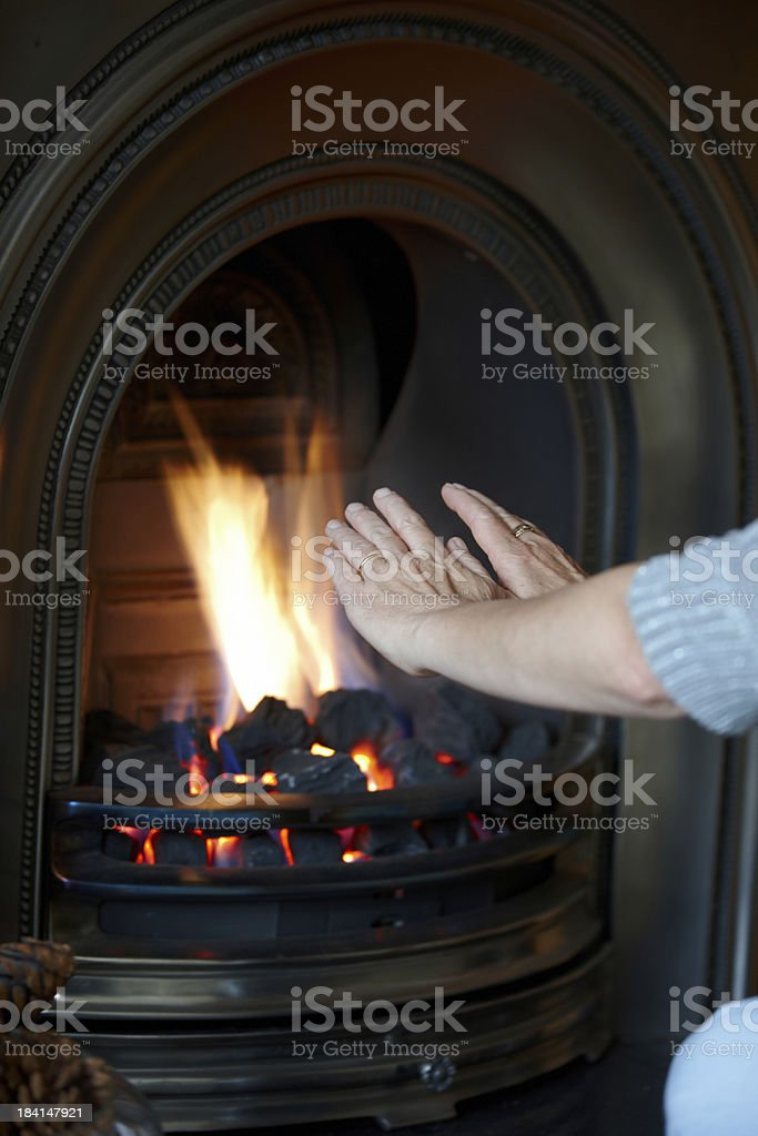 Mature woman warming hands by coal fire royalty-free stock photo