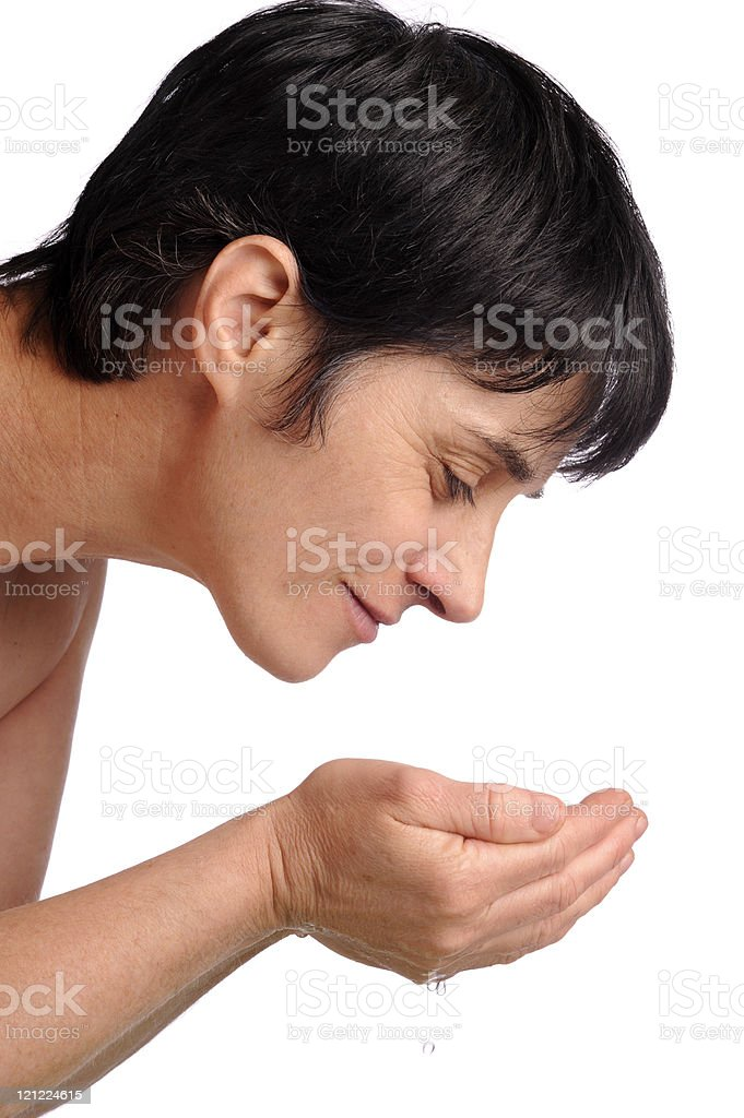 mature woman washing her face stock photo