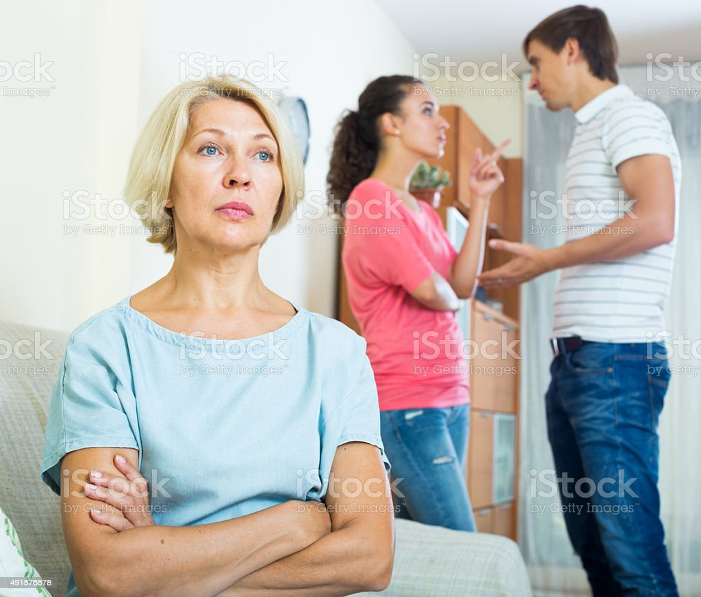 Mature woman watching young family couple quarrel at home stock photo