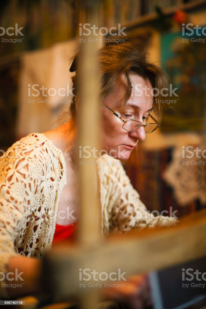 Mature woman waving on the antique loom. Traditional craft, Belarus, Eastern Europe. stock photo