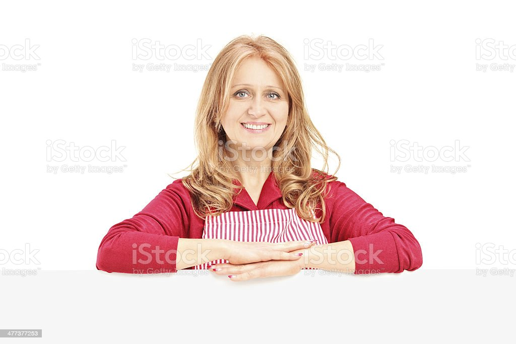 Mature woman wearing an apron and posing on blank panel royalty-free stock photo