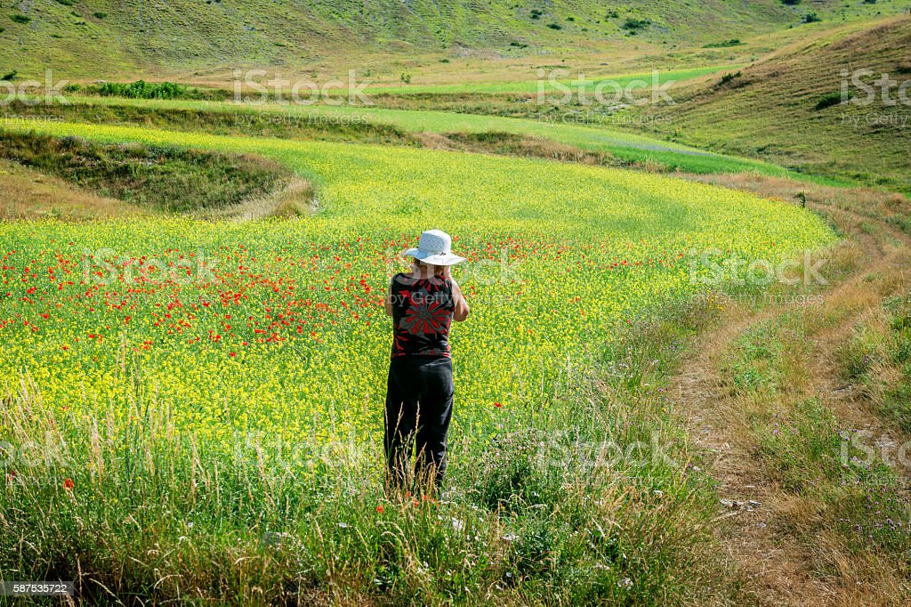 Mature Woman Wearing White Hat Photographing near Castelluccio, Italy stock photo