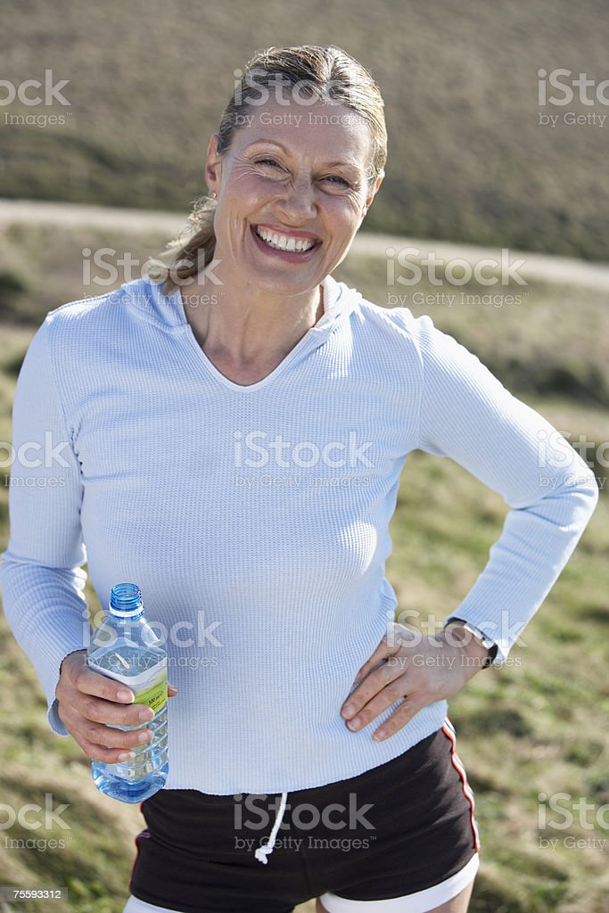 Mature woman with a bottle of water resting after a jog royalty-free stock photo