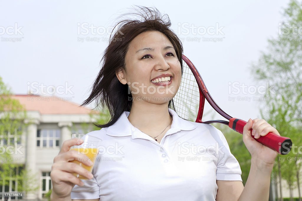 Mature woman with a smile holding tennis racket royalty-free stock photo