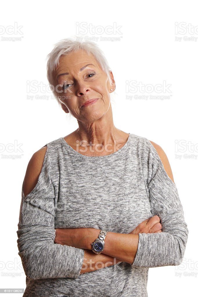mature woman with arms folded and head tilted stock photo