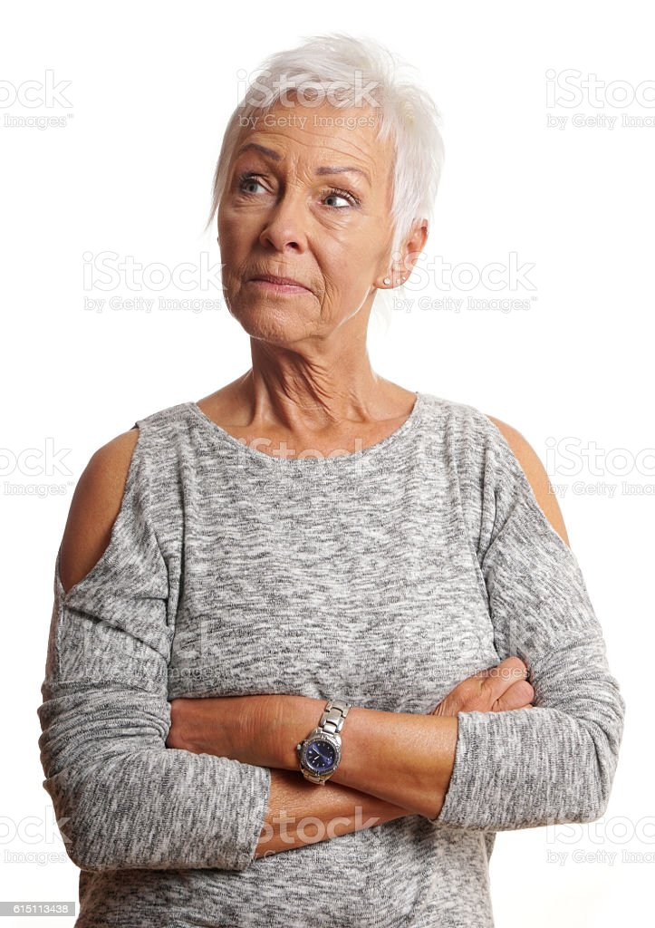 mature woman with arms folded looking away stock photo