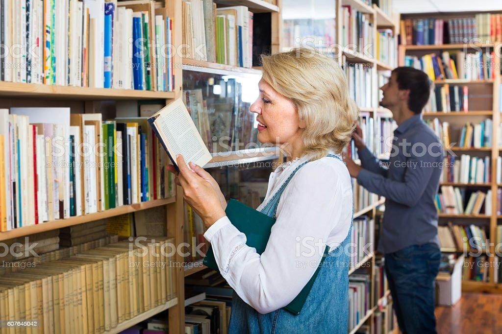 mature woman with book among bookshelves stock photo