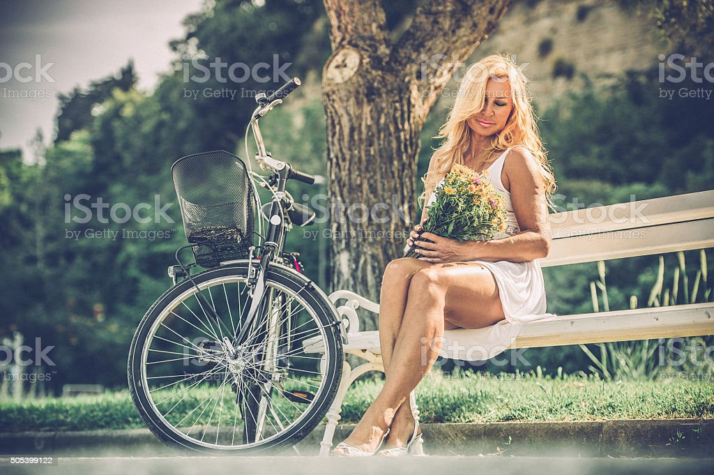 Mature woman with bouquet outdoors stock photo