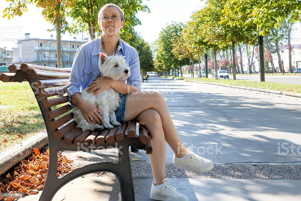Mature woman with dog on the bench stock photo