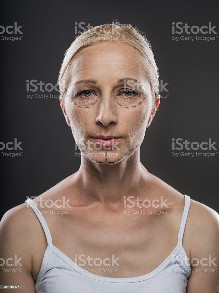 Mature woman with dotted lines on her face. stock photo