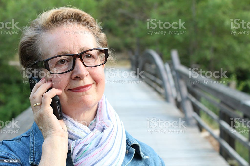 Mature woman with glasses calling outdoors stock photo
