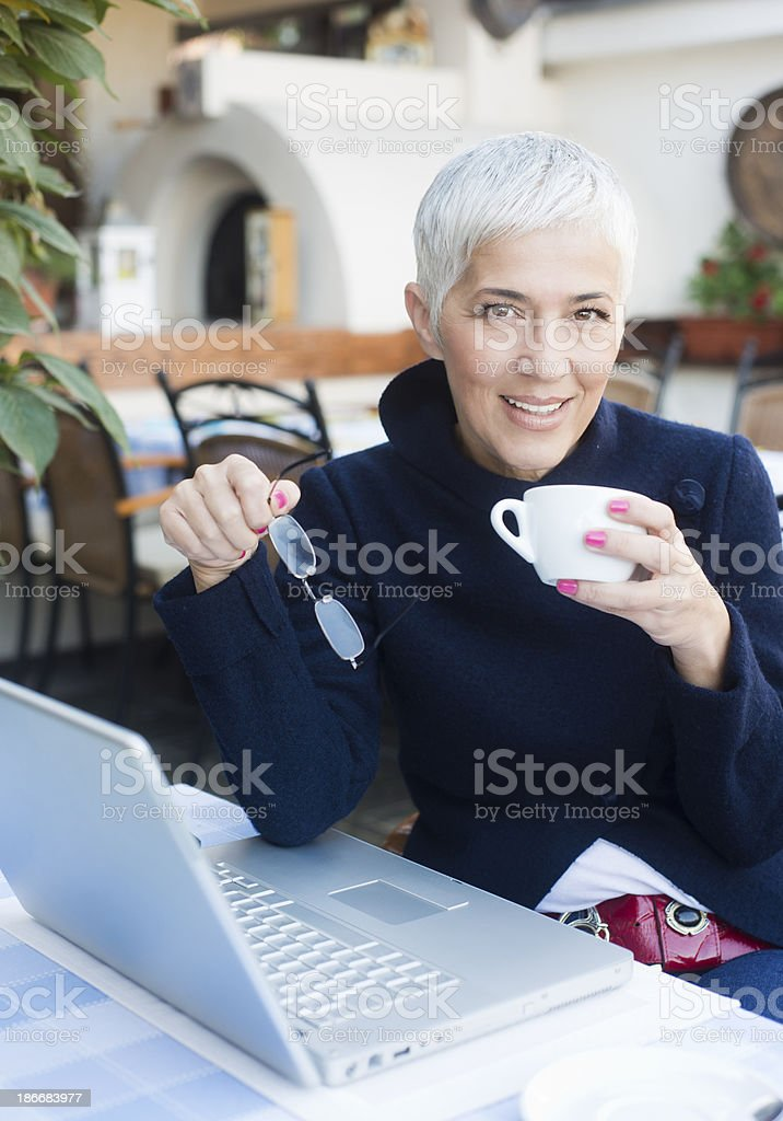 Mature woman with glasses using laptop at a cafe stock photo