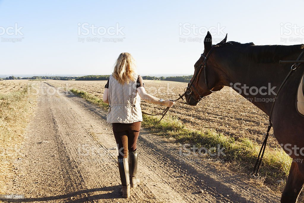 mature woman with her horse walking on rural path stock photo