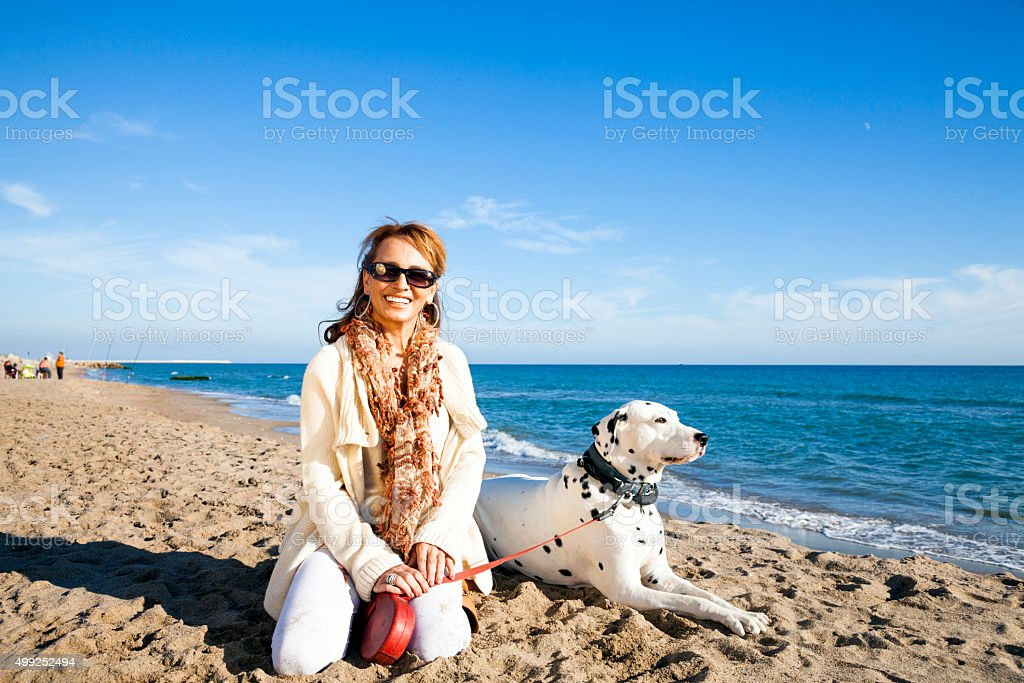 Mature woman with her loved dalmatian dog stock photo