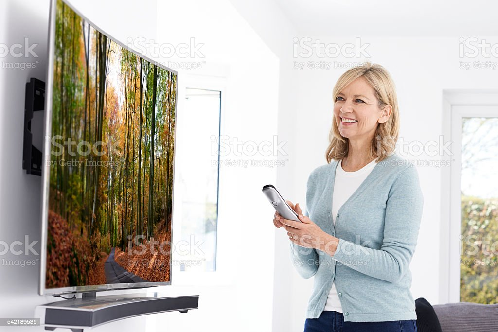 Mature Woman With New Curved Screen Television At Home stock photo