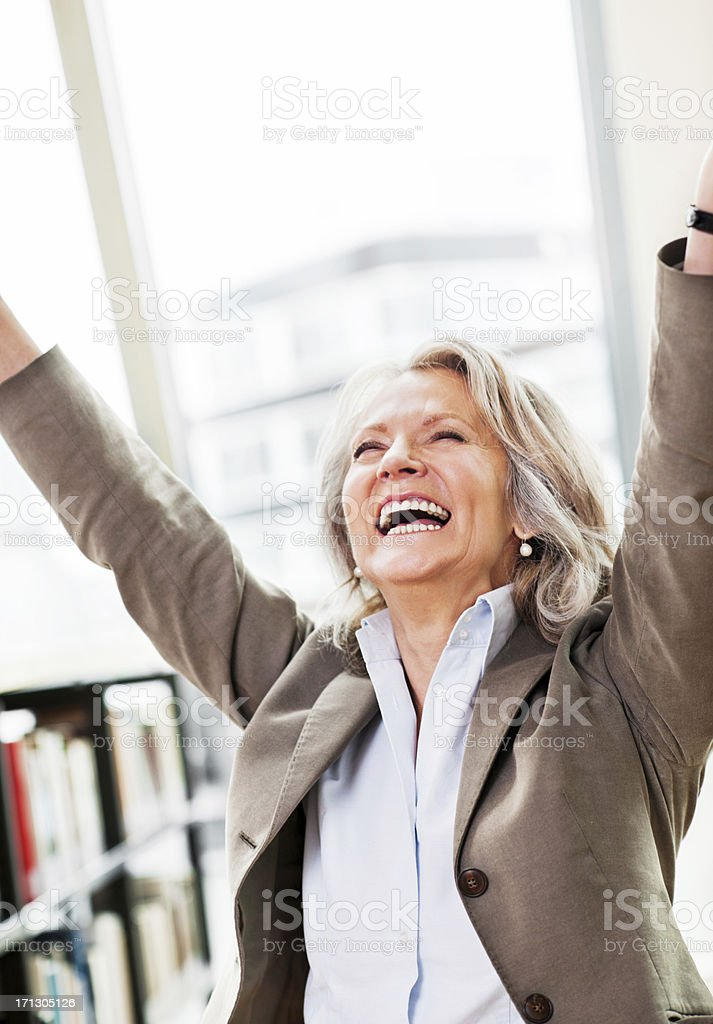 Mature woman with raised arms in a library. royalty-free stock photo