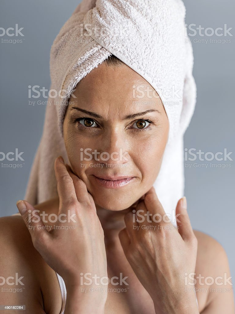 Mature woman with towel wrapped around her head. stock photo