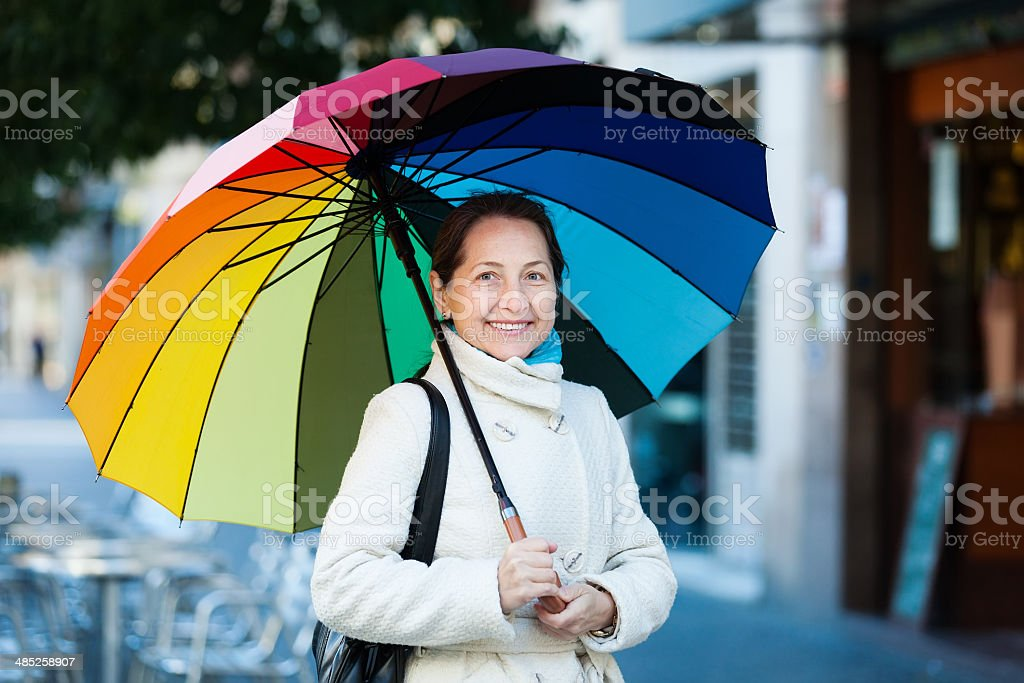 mature woman with umbrella in autumn stock photo