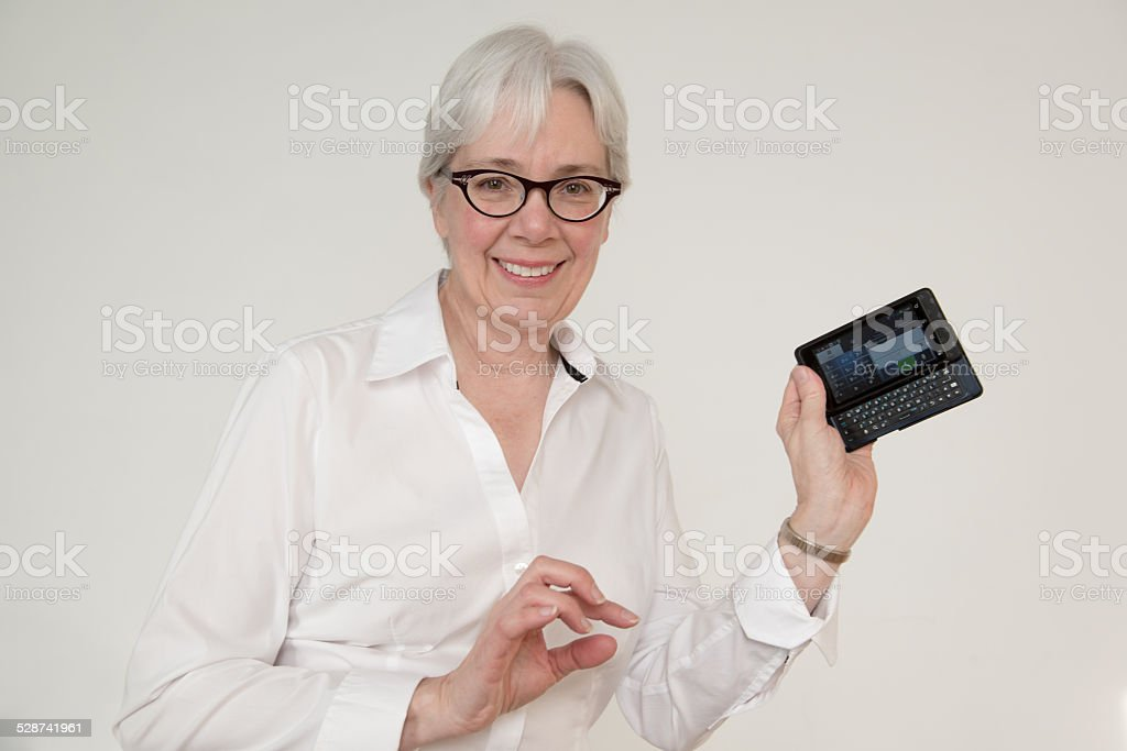 Mature woman with white hair shows off her smartphone stock photo