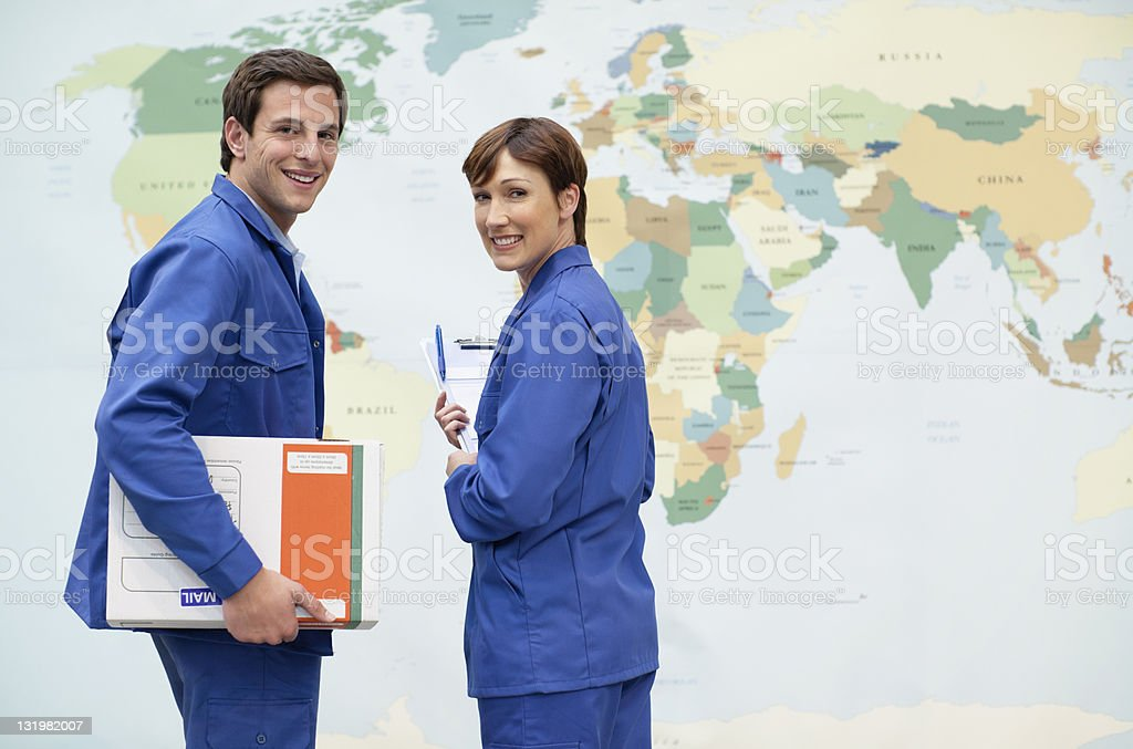 Mature woman with young man in front of world map stock photo