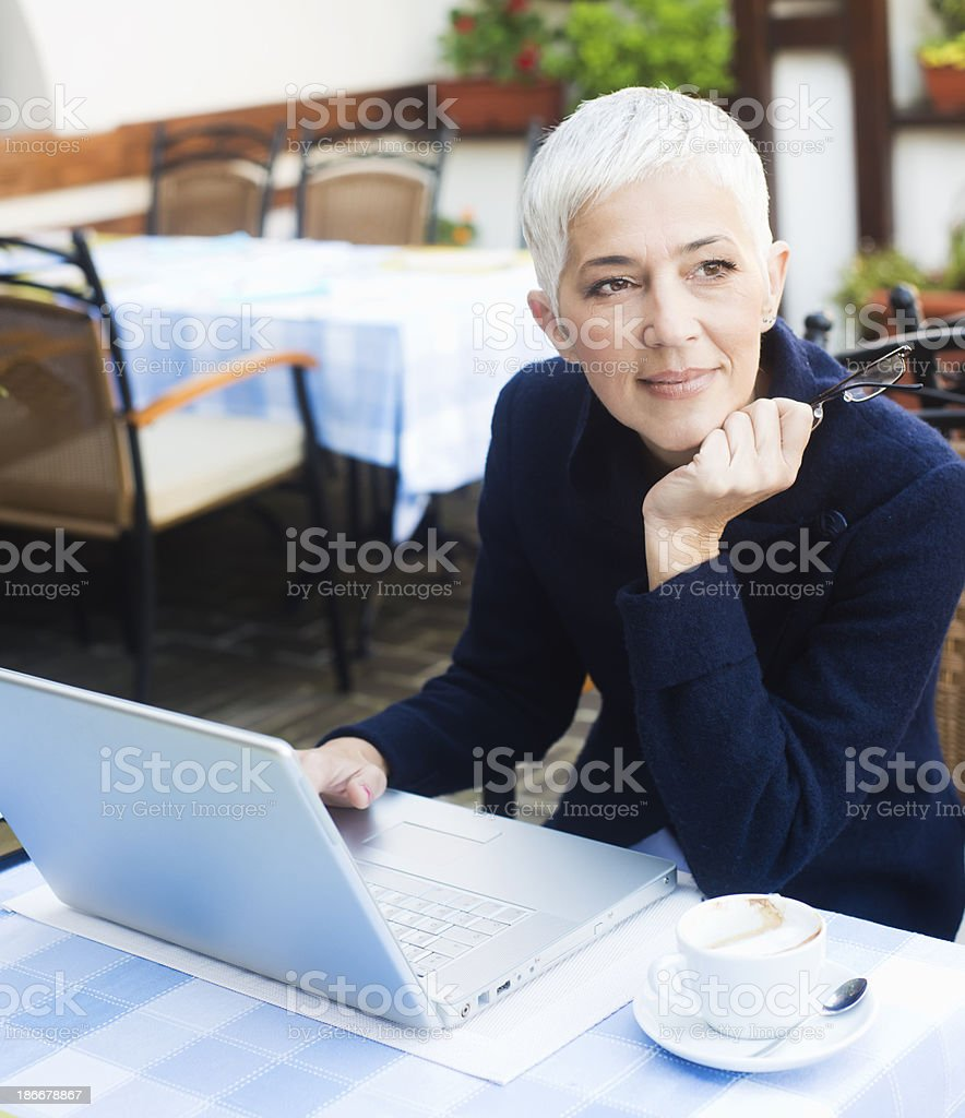 Mature woman working at caffe stock photo