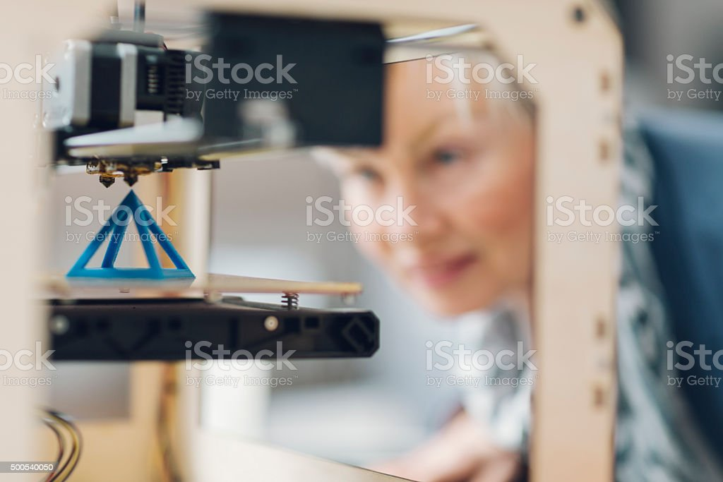 Mature Woman Working By 3D Printer in New Startup Office. stock photo