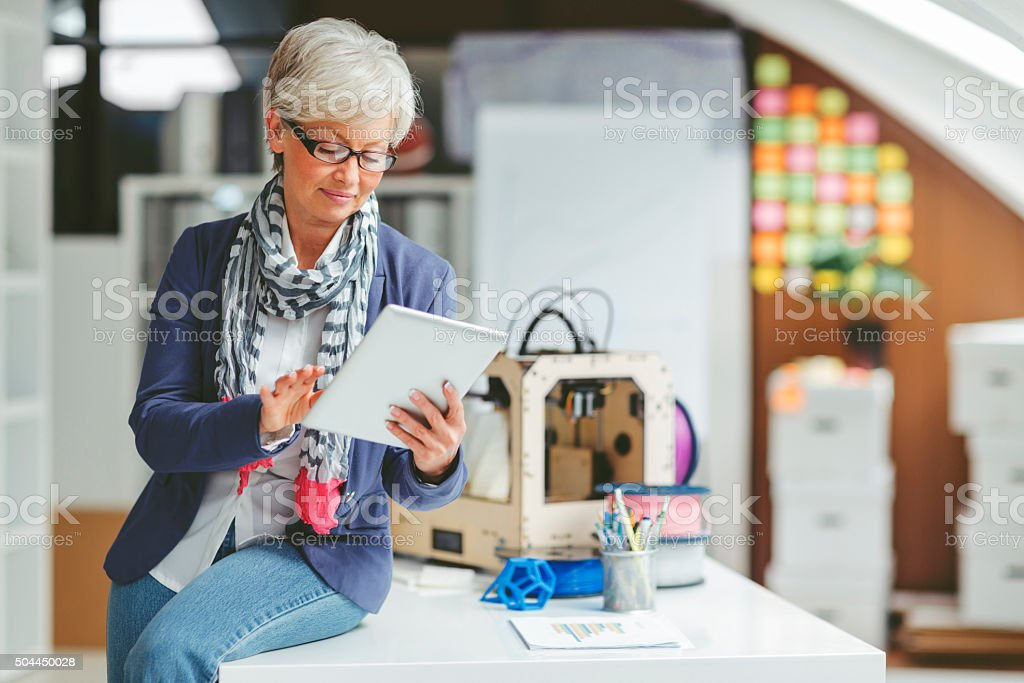 Mature Woman Working By 3D Printer stock photo