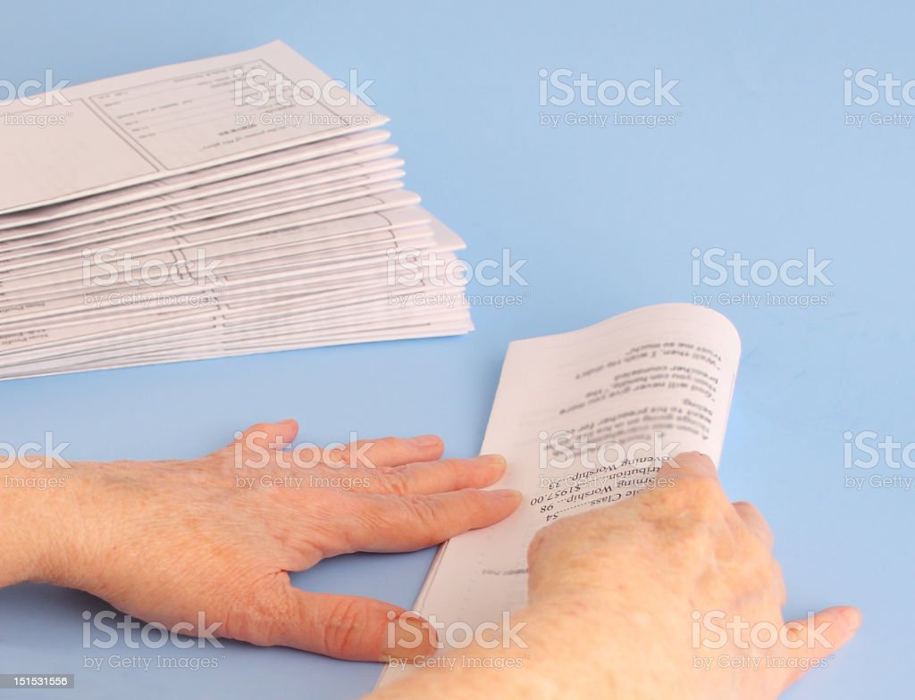 Mature Woman's Hands Folding Newsletters stock photo