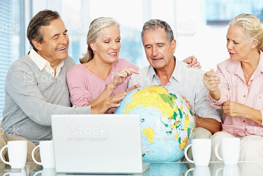 Mature women and senior men looking at globe royalty-free stock photo